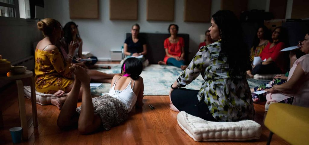 Latinx womxn sitting on the floor, some on cushions, others directly on the floor.