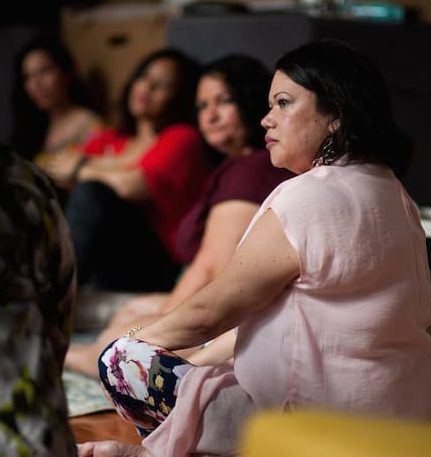 Latinx womxn in pale pink listens intently. She's in a circle, and other participants are a bit blurred.