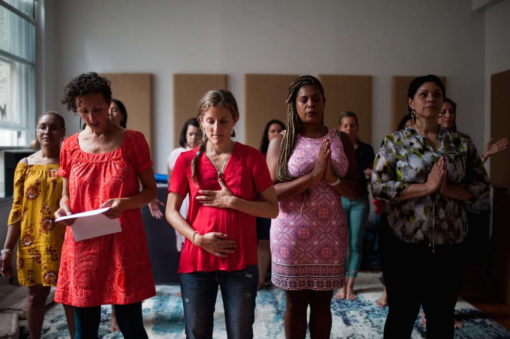 Latinx womxn standing, a few with hands in prayer position, another with hands on heart and belly. Isha stands reading from a paper.