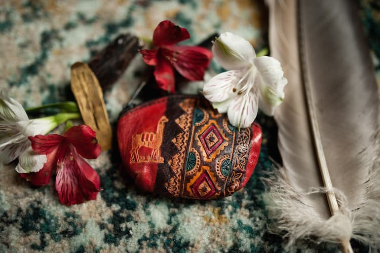 Red and white flowers, gray feather, piece of wood, leather decorated pouch set on carpet.