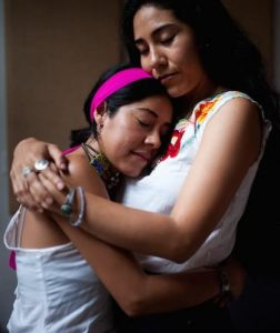 Two Latinx womxn hugging, eyes closed, in peace. Wearing white tops, jewelry; one has a bright pink headband.